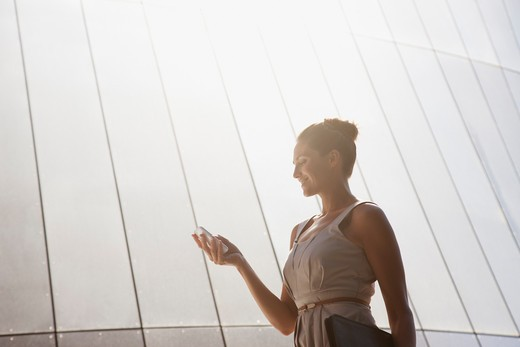 Stock Photo: 1775R-18744 Businesswoman text messaging on cell phone outdoors