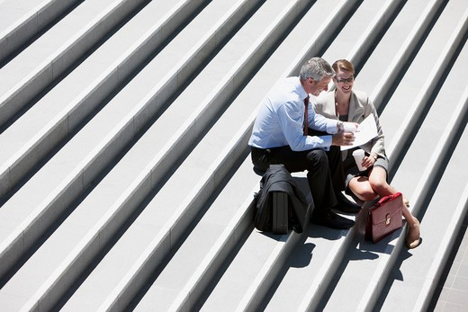 Business people sitting on steps talking outdoors : Stock Photo