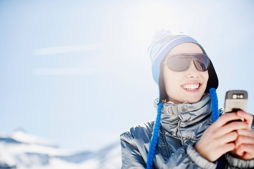 Woman using cell phone on mountain top : Stock Photo