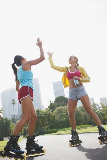 Women on rollerblades high fiving : Stock Photo