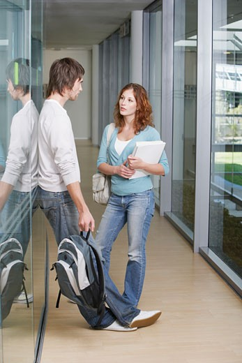 Young Woman and boy talking in corridor : Stock Photo
