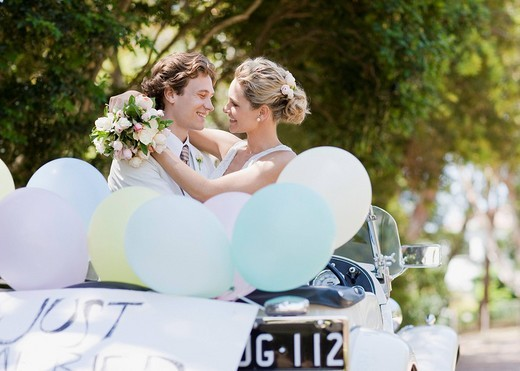 Bride and groom hugging in convertible : Stock Photo