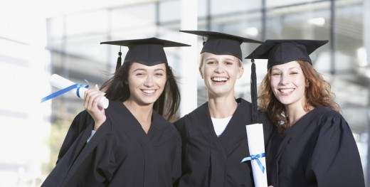 Young Adults in graduation gowns and mortar boards with diplomas : Stock Photo