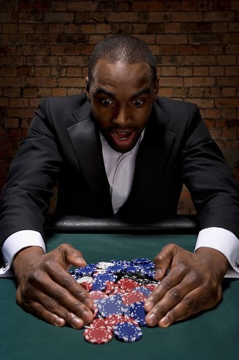 Man gathering poker chips in casino : Stock Photo