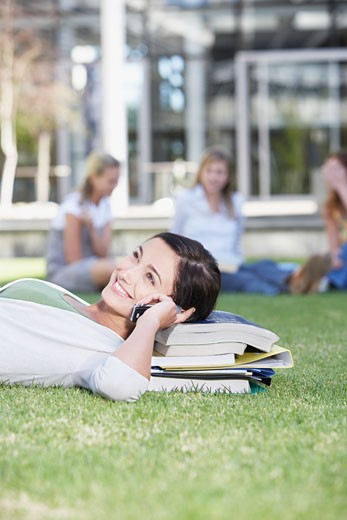 Young Woman laying down in grass on books with cell phone : Stock Photo