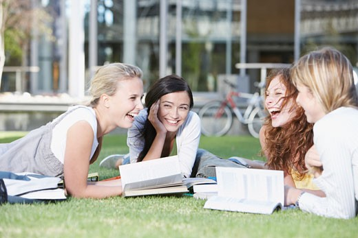 Stock Photo: 1775R-1977 Group of Young Women laying down on grass with books outdoors