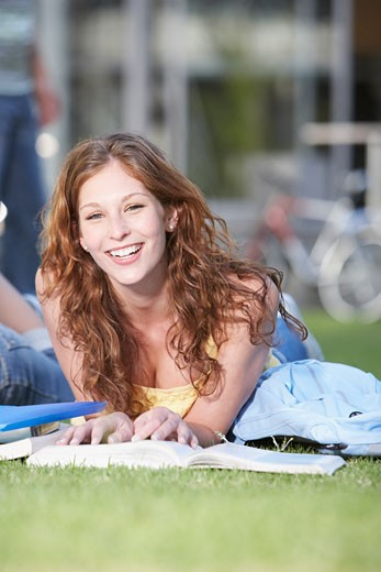 Stock Photo: 1775R-1980 Young Woman laying down on grass with books