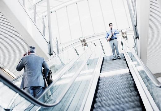 Businessman descending escalator : Stock Photo