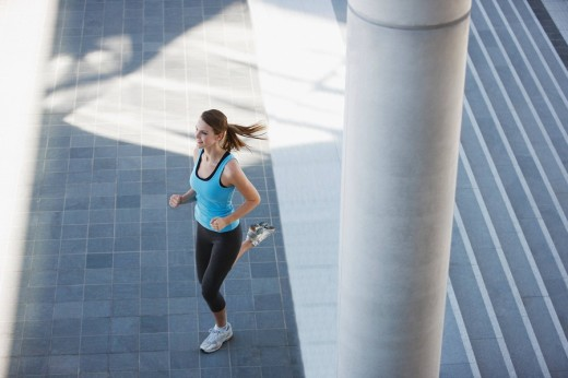 Woman running through urban setting : Stock Photo