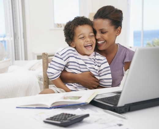 Mother and son at laptop laughing : Stock Photo