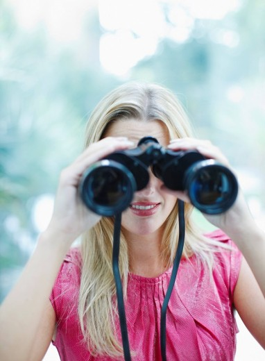 Woman using binoculars : Stock Photo