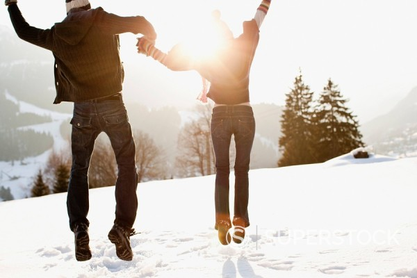 Stock Photo: 1775R-20165 Couple jumping outdoors in snow
