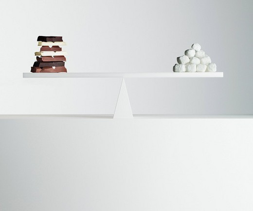 Chocolate bars and stack of sugar cubes balanced on seesaw : Stock Photo