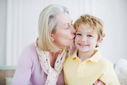 Grandmother kissing grandson's cheek : Stock Photo