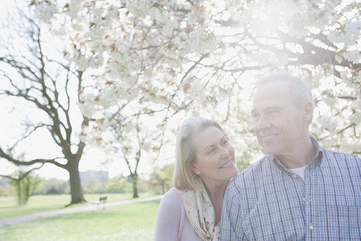 Smiling senior couple under blooming tree in park : Stock Photo