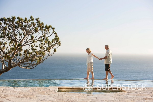 Senior couple holding hands along edge of swimming pool overlooking ocean : Stock Photo