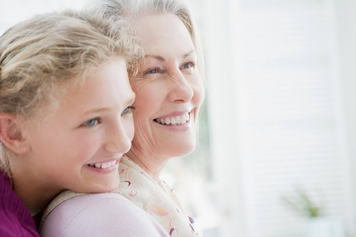 Smiling grandmother and granddaughter hugging : Stock Photo
