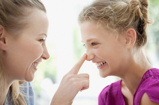 Smiling mother touching daughter's nose : Stock Photo