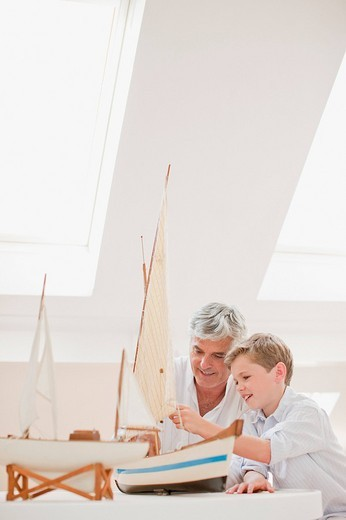 Father and son assembling model sailboat : Stock Photo