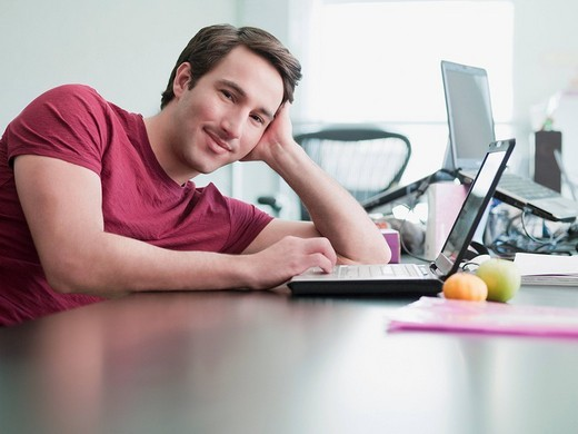 Smiling businessman using laptop and leaning on desk in office : Stock Photo