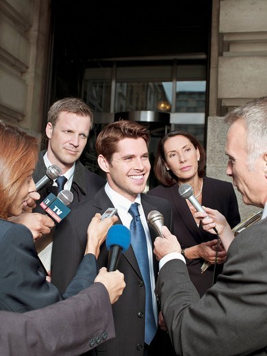 Stock Photo: 1775R-21086 News reporters interviewing smiling man outside courthouse