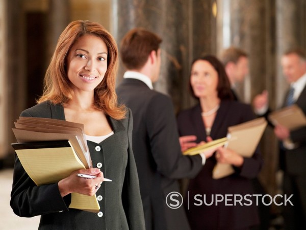 Smiling lawyer holding files in corridor : Stock Photo