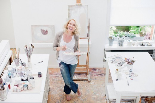 Woman holding paintbrush and palette in art studio : Stock Photo