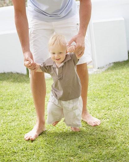 Stock Photo: 1775R-2119 Man teaching son to walk