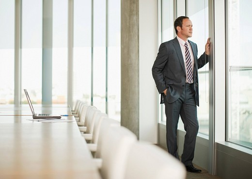 Pensive businessman standing at window of empty conference room : Stock Photo