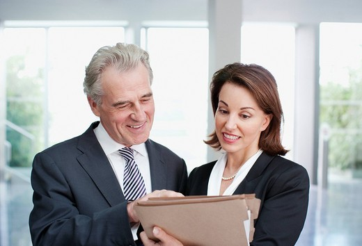 Stock Photo: 1775R-21254 Smiling business people reviewing file in office