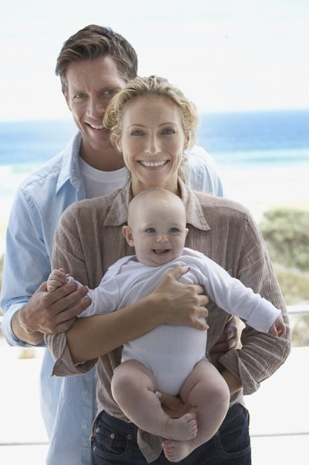 Man and woman holding baby outdoors : Stock Photo