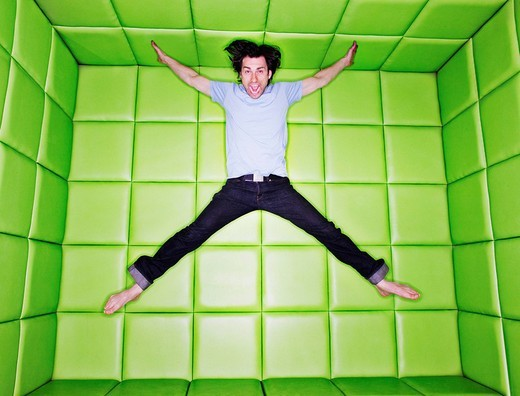 Man jumping in padded room : Stock Photo