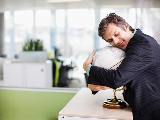 Smiling businessman hugging globe in office : Stock Photo