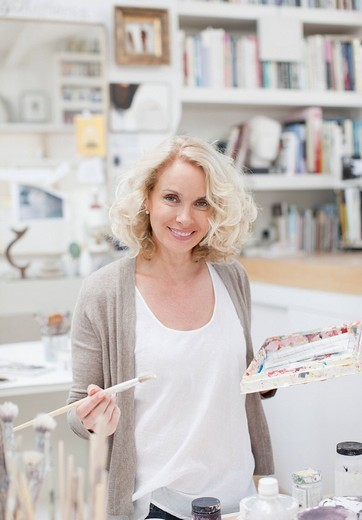 Stock Photo: 1775R-21582 Smiling woman holding paintbrush and palette in art studio