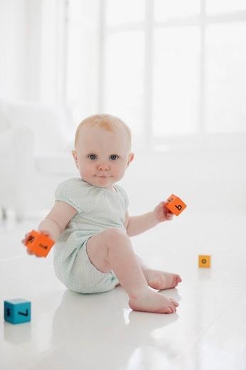Baby on floor with wood blocks : Stock Photo