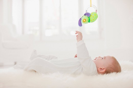 Stock Photo: 1775R-21669 Baby on rug reaching for hanging toy overhead