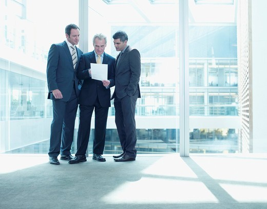 Businessmen reviewing paperwork near glass wall in office : Stock Photo