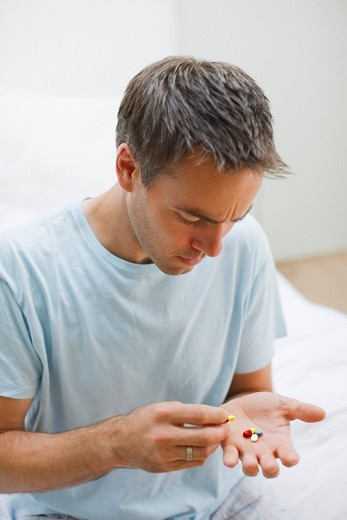 Man holding pills and counting them : Stock Photo