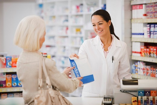 Pharmacist handing customer prescription in drug store : Stock Photo
