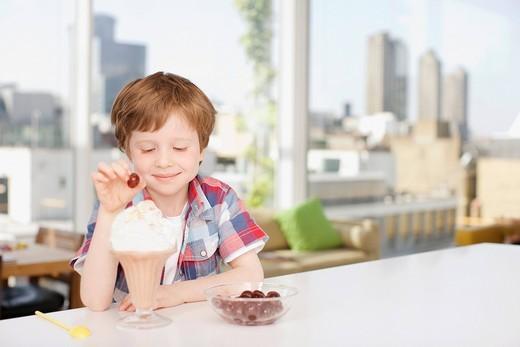 Smiling boy putting cherry on ice cream sundae : Stock Photo