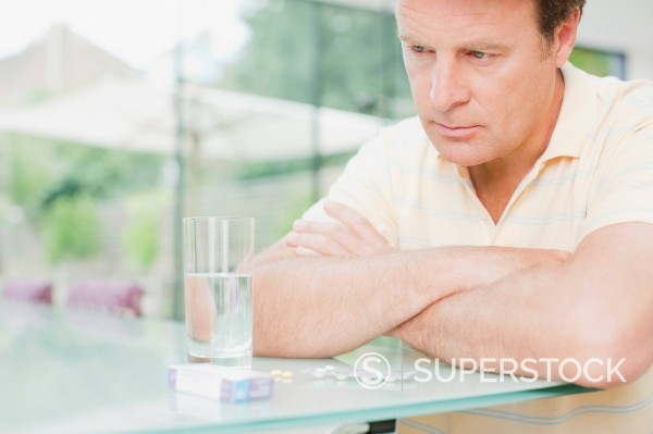 Stock Photo: 1775R-21959 Man sitting with glass of water and box of pills