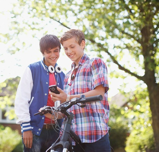 Teenage boys looking at cell phone together : Stock Photo