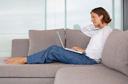 Woman on sofa with laptop : Stock Photo