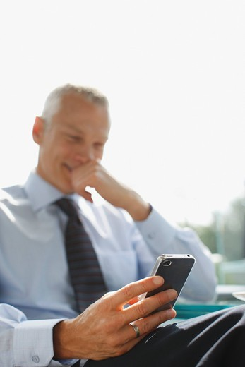 Stock Photo: 1775R-22127 Businessman text messaging on cell phone