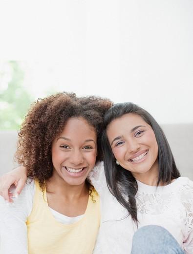 Smiling teenage girls hugging : Stock Photo
