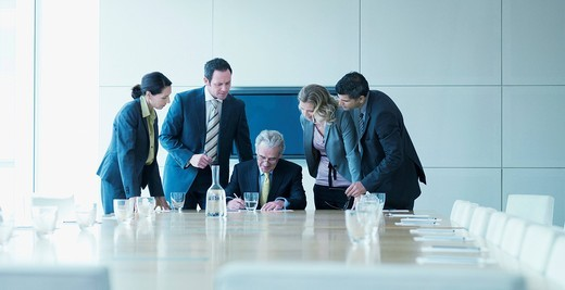 Business people watching boss sign contract : Stock Photo