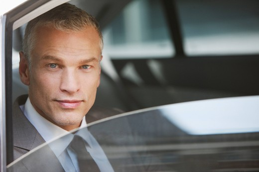 Stock Photo: 1775R-22255 Businessman sitting in back seat of car