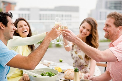 Stock Photo: 1775R-22464 Laughing couples toasting with Champagne outdoors