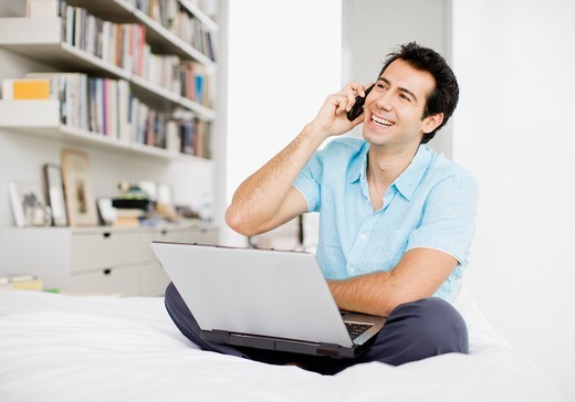 Smiling man sitting on bed using laptop and cell phone : Stock Photo