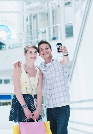 Stock Photo: 1775R-22504 Smiling couple taking self_portrait in shopping mall